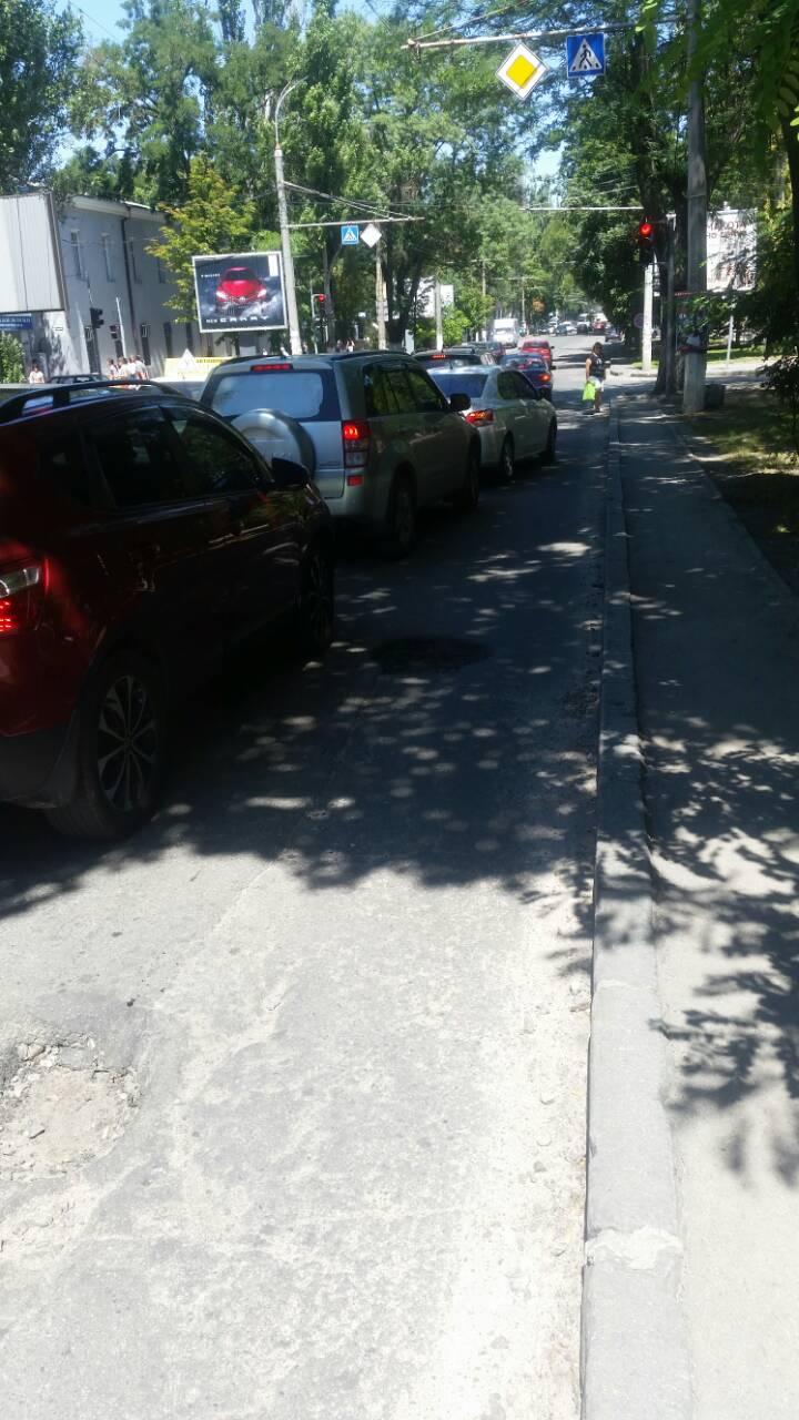 В центре Херсона несколько активистов и полиция измеряли глубину ямы в дороге